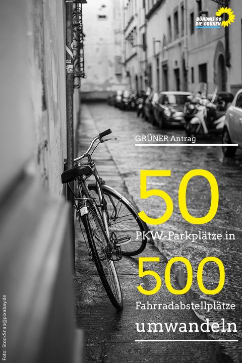 Fahrrad an Hauswand, geparkte Autos am anderen Straßenrand